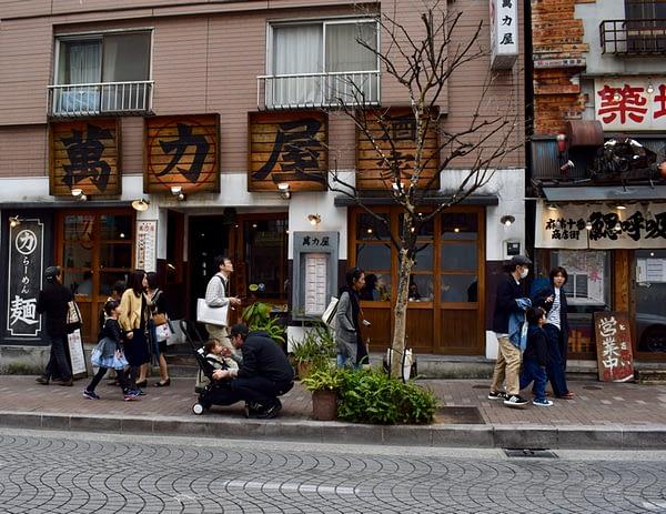 Exterior shot at Man Riki Ya Noodle shop with lots of people Azabujuban Tokyo Japan